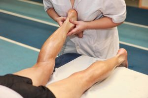 masseuse massaging athlete' s Achilles tendon after running - tendinites